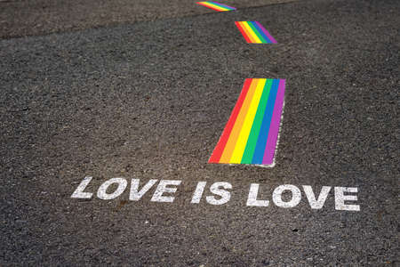 Love is love written on black asphalt road and white rainbow flag marking lines, Happy pride diversity concept and love is love idea