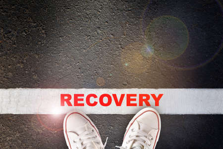 Recovery word written on asphalt road surface with white starting lines. Economic and business challenge concept with effort idea