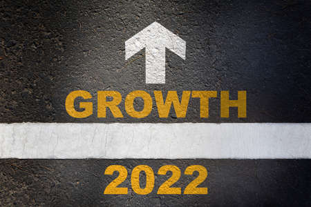 New year 2022 growth and white arrow written on asphalt road surface with white starting lines. Target challenge to success concept and keep moving idea