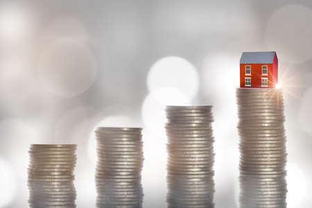 Mortgage and productive real estate investment concept and financial saving idea. House model on stack of money coins for loan, refinance and retirement