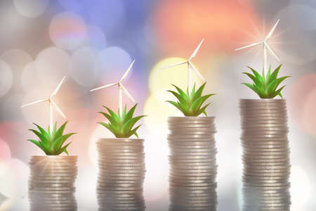 Return on investment on renewable clean energy for sustainability concept and alternative energy economic growth idea. Growing money plant and turbine on stack of coins on abstract background Reklamní fotografie