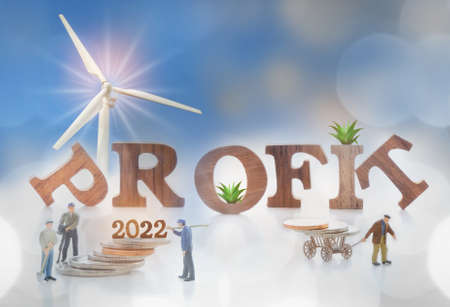 Wooden profit and 2022 with growing money plant on stack of coins with miniature worker and turbine background. Renewable clean energy investment for sustainability concept and alternative energy idea