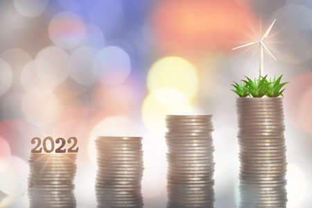 2022 return on investment on renewable clean energy for sustainability concept and alternative energy economic growth idea. Growing money plant and turbine on stack of coins on abstract background Reklamní fotografie - 165651784
