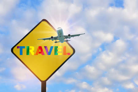 Airplane travel and colorful rainbow travel word written on yellow sign on beautiful blue sky with fluffy cloud background. Rainbow lesbian gay bisexual transgender concept and equality diversity idea Reklamní fotografie