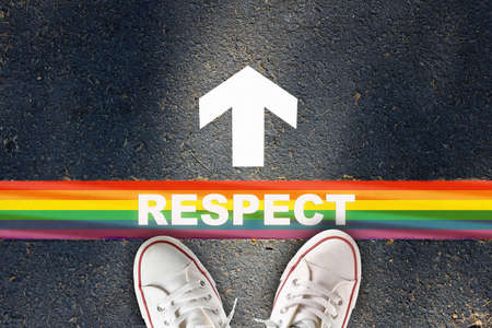 Respect written on rainbow line marking with white arrow sign with on asphalt road. Lesbian gay bisexual transgender concept and equality diversity idea Reklamní fotografie