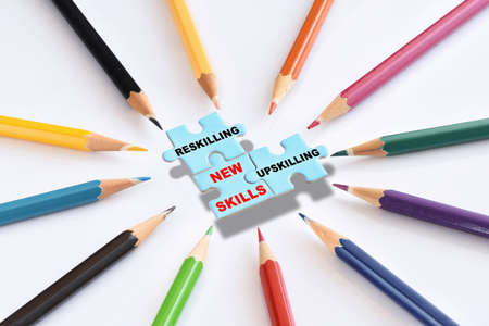 New skills development concept and changing skill demand idea . Reskilling, upskilling and new skills written on blue puzzle with colored pencils isolated on white background