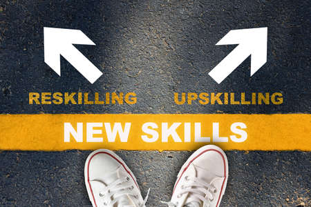 New skills development concept and changing skill demand idea. New skills written on yellow line with reskilling and upskilling with white arrow on asphalt road Banque d'images