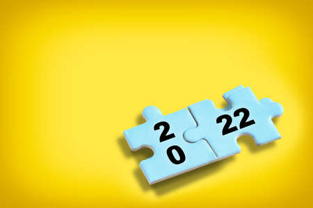 New year 2022 on blue puzzle with shadow on yellow background, business success concept and challenge idea