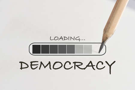 Democracy loading written on white paper with processing symbol and pencil