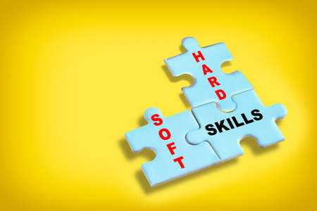 Soft skills and hard and skills written on blue puzzle jigsaw with shadow on yellow background. Behavior and thinking concept