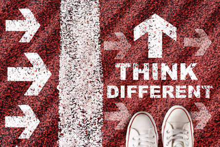 Think different written on red road running with white arrows and marking lines. Self esteem with direction concept and passion idea