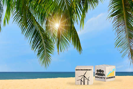Environment society and economics written on wooden cube with coconut palm leaves on tropical beach with cloudy sky background. Sustainable development concept and future ahead idea Stock fotó