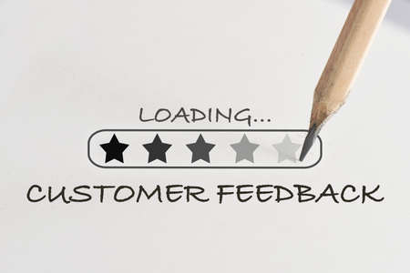 Customer feedback with stars loading written on white paper with processing symbol and pencil. Service rating satisfaction concept and five star review idea Stock fotó
