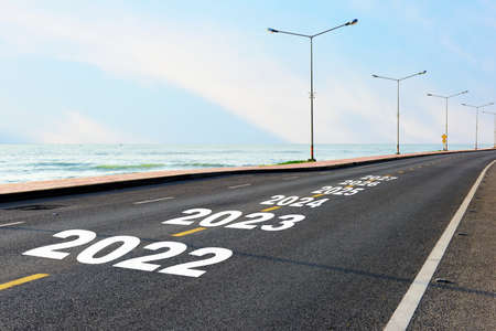 New year 2022 to 2027 on asphalt road with marking line for given direction and sea landscape. Summer travel holiday concept and road to recovery idea Stock fotó