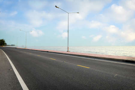 Empty asphalt road with marking line for given direction and sea landscape. Transportation concept and summer travel holiday idea Stock fotó