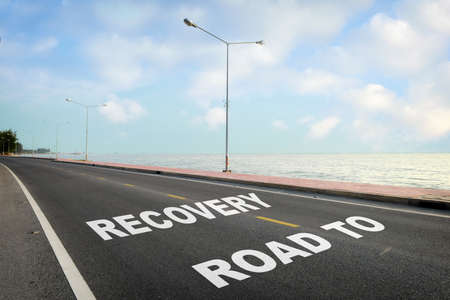 Road to recovery written on asphalt road with marking line for given direction and sea landscape. Stock fotó