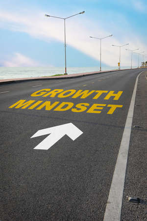 Growth mindset with white arrow marking on road surface. Self development to success concept and business challenge idea
