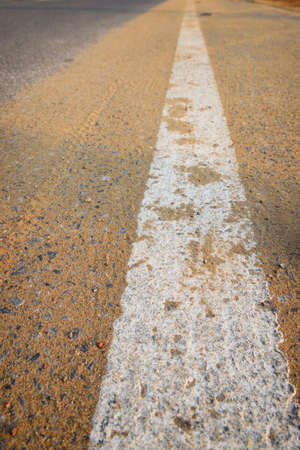 Closeup empty asphalt road with sand and white marking line for given direction. Abstract adventure background concept and transportation idea Stock fotó