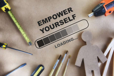 Empower yourself written on brown background with tools supplies and paintbrush. Optimism personality concept and challenge idea Reklamní fotografie