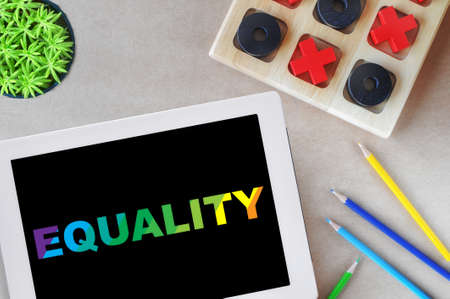 Equality word on digital computer tablet with colored pencils and tic tac toe game on workspace background. LGBT human concept and diversity freedom idea