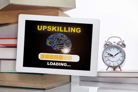 Upskilling loading with brain on digital computer tablet with stack of textbook with time to change words on alarm clock isolated on white background. Technology transformation concept and time management idea
