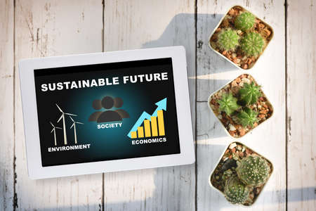 Sustainable future environment protection society and economics on computer tablet with cactus on desk background. Clean energy to sustainable future concept and alternative energy idea