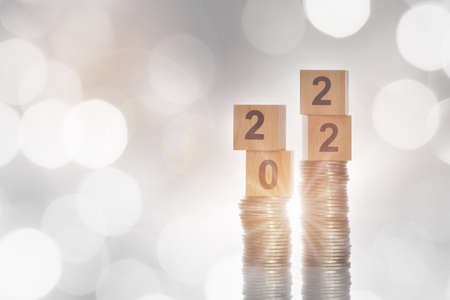 Number 2022 and stack of coins glowing on abstract background. Saving with return on investment concept and new year sustainable economic growth idea Reklamní fotografie