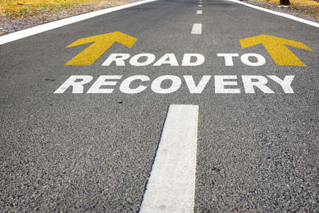 Road to recovery words and yellow arrow on road. Economic recovery concept and business challenge idea