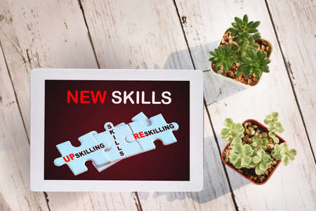 Start to education new skills on computer digital tablet screen with cactus and succulents plant on wooden white background. Online technology concept and digital machine learning idea