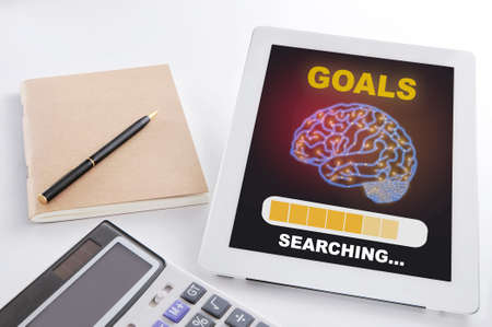Goals searching with brain on digital computer tablet on busy working desk. Self esteem concept and passion with efficiency idea