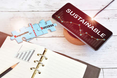 Sustainable business and finance technology on smart phone screen with growth graph on wireless charger with responsible business success written on blue puzzle on desk. Artificial intelligence machine learning concept and sustainability solution idea Reklamní fotografie