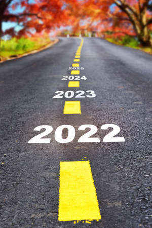 Happy new year concept and business beginning with challenge  idea. Journey to new year 2022 to 2025 on asphalt road surface with autumn season Reklamní fotografie