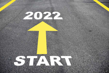 Start 2022 and yellow arrow on asphalt road surface. Business challenge concept and keep going idea