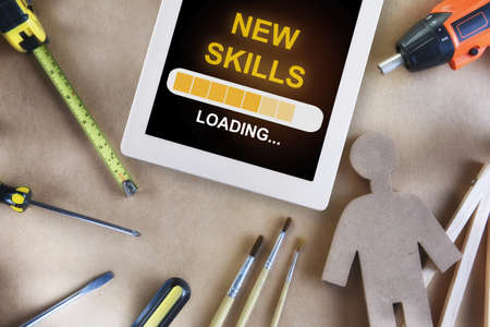 New skills loading on digital computer tablet and tools supplies on wooden background. Reskilling and upskilling concept and technology transformation learning model idea Reklamní fotografie