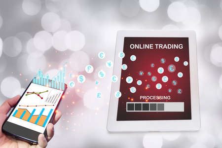 Investment stock market trading using smart phone and digital computer tablet on bokeh background. Financial technology fintech concept and machine learning transformation idea Reklamní fotografie