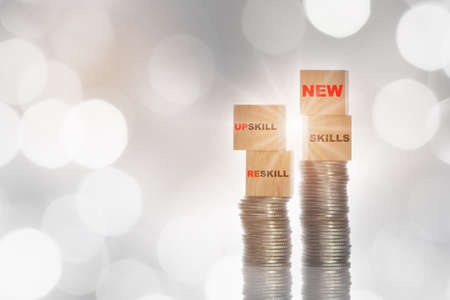 New skills, reskill and upskill written on wooden cube and stack of coins glowing on abstract background. Sustainable economic growth concept and empower with mindset idea Reklamní fotografie