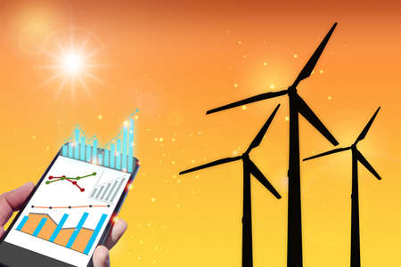 Sustainable business and banking concept with alternative energy economic growth idea. Growth graph investment on smart phone and wind turbine clean energy on orange shade color background