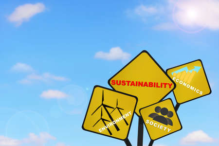 Environment, society and economics written on yellow sign on beautiful blue sky with fluffy cloud background. Save the earth concept and inspiration and motivation idea