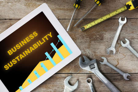 Business sustainability written on computer digital tablet with tools supplies on wooden background. Sustainable future to success concept and challenge idea