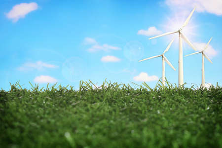 Wind turbine on green grasses on beautiful fluffy cloud and blue sky background. Clean energy to sustainable future environment concept and alternative energy economic growth idea
