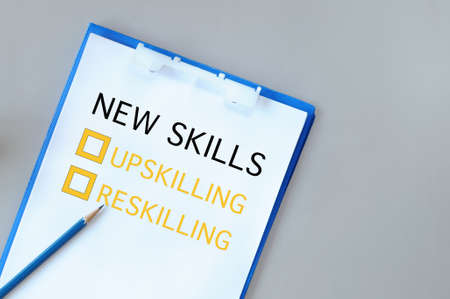 Upskilling and reskilling with check box on notepad with paper and pencil on grey background. New skills for success concept and education learning challenge idea