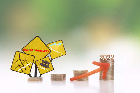 New year 2022, environment, society and economics written on yellow sign on stack of coins with red arrow upwards on abstract background. Sustainable with return on investment concept and economic growth idea