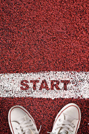 Top view of start word on starting line and white sneaker on red sport track. Business success concept and challenge idea