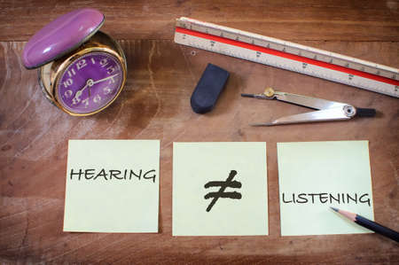 Hearing not equal listening written on sticky notes with alarm clock on wooden table. Communication with understanding concept and soft skill idea Reklamní fotografie