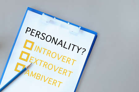 Personality introvert, extrovert and ambivert with check box on notepad with paper and pencil on grey background. Human personality type concept and shy or outgoing person idea Reklamní fotografie