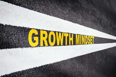 Growth mindset on asphalt road with marking lines for giving directions. Business success with future ahead concept. Self development to new skills