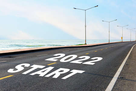 Start new year 2022 on asphalt road with marking line for given direction and sea landscape. Road to recovery concept and business success idea Reklamní fotografie