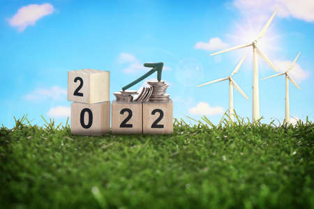 New year 2022 and stack of coins with wind turbine on green grasses on fluffy cloud background. Clean energy to sustainable future environment concept and alternative energy economic growth idea Reklamní fotografie