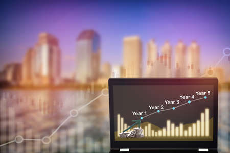 Uptrend and bull market trading concept and real estate idea. Stock market trading profit and return on investment on computer laptop on growth graphs on modern business building background