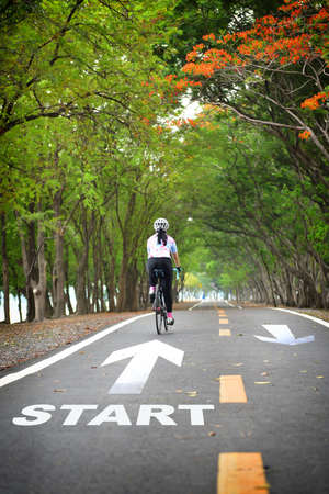 Start word with sportswoman ride bike on road with white arrow. Journey to success concept and keep going idea